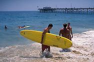 Lifeguard carries a surfboard on beach near Balboa Pier, Balboa Island, Newport Beach, California