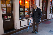 Street scene in Chinatown, London, UK. An elderly Chinese man walks steadily past one of the many restaurants in this area.