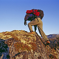 A hiker scrambles over a boulder in mountainous tundra.