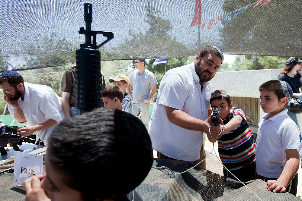 Israeli children play with rifles and pistols during a traditional display of military weapons, part of the celebrations for Israel's Independence Day marking the 63rd anniversary of the creation of the state, at the Ammunition Hill national memorial site in Jerusalem on May 10, 2011.