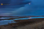 Moon setting at dawn at Freezeout Lake WMA near Choteau, Montana, USA