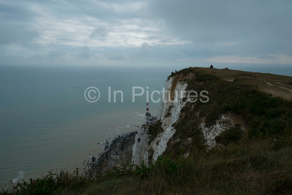 View out to sea and the English Channel from Beachy Head clifftop just outside Eastbourne, England, United Kingdom. Beachy Head is a chalk headland in East Sussex, situated immediately east of the Seven Sisters. The cliff is the highest chalk sea cliff in Britain, rising to 162 metres above sea level and is hence known as a prime location for suicides. Some people get precariously near to the edge.