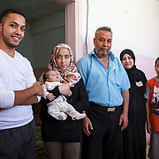 Judge Khalid, 48, and his family arrived in Jordan almost three years ago from Homs, Syria. Judge Khalid is a community leader in Mercy Corps' conflict resolution program for Syrian refugees and Jordanians in Mafraq, Jordan. The program helps build a peaceful community between the two groups.<br /> <br /> Khalid and his family fled bombings so quickly, they had no time to bring any material things with them. The most important thing Khalid brought with him is his family. Mafraq, Jordan, May 2015.