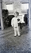 little child holding a doll in the garden 1920s
