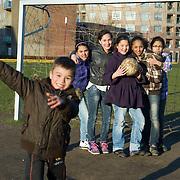 Nederland Rotterdam 7 maart 20110 20110307 Achterstandswijk Katendrecht. Jonge meiden spelen een potje voetbal in de wijk op het grasveld en poseren met voetbal voor de fotograaf.  Deelgemeente Feijenoord,.Oud Zuid, omvat 4 probleemwijken die waarvan 1 Katendrecht. , speel plek lokatie, speellokatie, speelplaats, speelplein, speelpleintje, speelplek, speelplekken, speelruimte, speelse, speelveld, speelveldje, spelen, spelende, spelenderwijs, sport, sportief, sportieve, sportive, stadsdeel, stadse, stadswijk, stedelijke, straatvoetbal, tezamen, together, ventje, vitaal, vitale, vitaliteit, voetballen, voetballer, voetballers, voetballertjes, voetbalpleintje, voetbalveld, voetbalveldje, vogelaarbuurt, vogelaarbuurten, vogelaarwijk, vogelaarwijken, vrienden, vriendin, vriendinnen, vriendschap, vriendschappelijk, vriendschappelijke omgang, vrolijk, vrolijke, westerse allochtonen, westerse allochtoon, wijk, wijken, woonbuurt, woonbuurten, woonwijk, woonwijken, zichzelf vermaken, zonnig weer, zonnige dag Foto: David Rozing