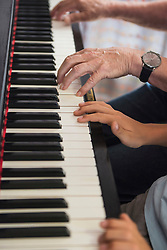 Hands of grandfather and grandson playing piano, Eichenau, Bavaria, Germany