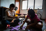 """31 MARCH 2013 - BANGKOK, THAILAND:     Nailintip """"Bang"""" Cheunchum, 12, (RIGHT) helps Michelle Kao (LEFT) cut out crosses construction paper before Easter services at the Thai Peace Foundation office in the Bangkapi section of Bangkok.     PHOTO BY JACK KURTZ"""
