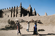 Women carry firewood past the impressive mud walled Grand Mosque, in Djenne, Mali.