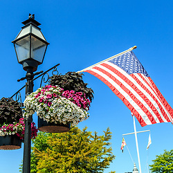 Annapolis, MD / USA - July 9, 2017: A US Flag on a pole with plants at the dock in the harbor area of Maryland's capital city.