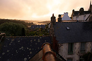 Sunset view looking over rooftops along the tidal Goyen River on 17th September 2021 in Pont Croix, Brittany, France. Brittany is a peninsula, historical county, and cultural area in the west of France, covering the western part of what was known as Armorica during the period of Roman occupation. It became an independent kingdom and then a duchy before being united with the Kingdom of France in 1532 as a province governed as a separate nation under the crown.