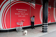 A dog owner checks messages with his pet on a lead outside the John Lewis department store in central London, on 15th July 2019, in London, England.