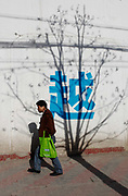 """A man walks past a shadow of a tree on a wall with the Chinese character """"Yue"""" in Shanghai, China on 26 January, 2009."""