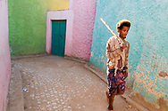 Young man walking the colorful streets of Harar. Every year the inhabitants of the city, during the Ramadan holidays, completely repaint their houses with bright colors.