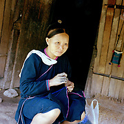 A Lanten ethnic minority woman sews traditional clothing outside her home, Ban Nam Chang, Bokeo province, Lao PDR. The Lanten or Yao Mun are a small but distinctive group of the Yao ethnic minority residing in northern Laos, Vietnam and China.  Maintaining a strong cultural identity, they are easily recognised by their hand woven, indigo dyed attire. Unlike many other ethnic groups who have relinquished their traditional dress, each Mun family still cultivates cotton and indigo for spinning, weaving, dyeing and sewing into clothing. One of the most ethnically diverse countries in Southeast Asia, Laos has 49 officially recognised ethnic groups although there are many more self-identified and sub groups. These groups are distinguished by their own customs, beliefs and rituals.