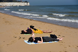 © Licensed to London News Pictures. 20/04/2019. BROADSTAIRS, UK.  Women relax in the sunshine during the unusually warm weather at the seaside near Broadstairs in Kent.  The forecast is for the Easter bank holiday weekend to be even warmer.  Photo credit: Stephen Chung/LNP