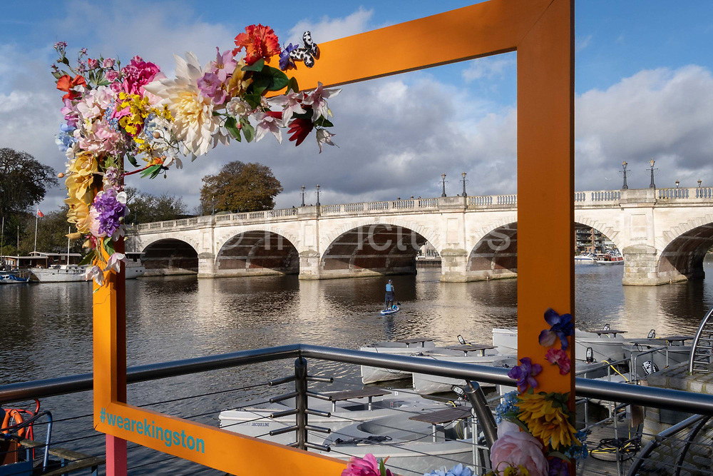 Seen through a rectangular #wearekingston picture frame, a middle-aged man paddles on the surface of the Thames River towards Kingston Bridge at Kingston-upon-Thames, on 12th November 2020, in London, England.