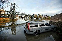 © Licensed to London News Pictures. 22/12/2019. Thames Ditton, UK. A car sits in flood water on the bank of the The River Thames which has burst it's banks at Thames Ditton, Surrey. Further weather warnings are in place following flooding and high winds in parts of the UK . Photo credit: Ben Cawthra/LNP
