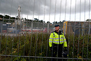 Balcombe, West Sussex. Site of Cuadrilla drilling. Demonstration against fracking 18.08.2013. A policeman stands behind the security fence with the drilling rig in the background.