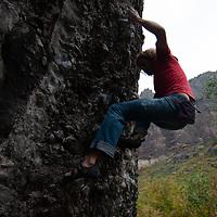 A rock climber boulders on a rock near Telluride, Colorado.
