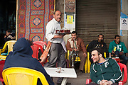 Young men sit and talk outside the Gold Star cafe, Cairo, Egypt