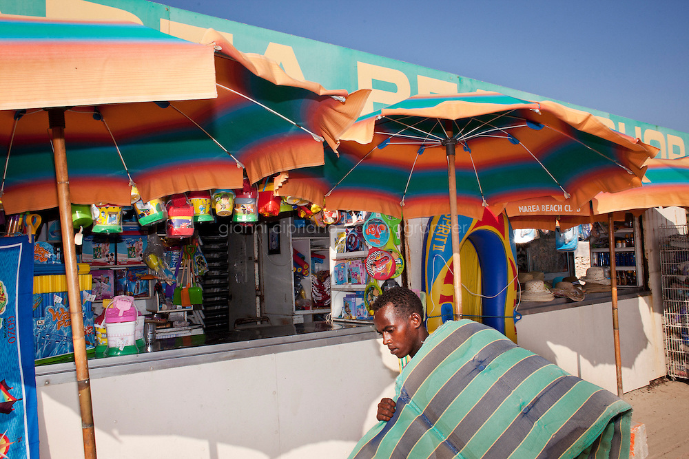 """Mellieha, Malta - 19 August, 2012:  Hassan Mahamed Dalmar, 21, an immigrant from North Somalia, carries cushions in front of the kiosk he works for at the Mellieha Bay beach, Malta, on 19 August, 2012. Hassan left Somalia in 2007 and went to Djibouti, Eritrea, Sudan, Libya and arrived in Malta in 2009 after paying a smuggler $900 to board a boat with 160 immigrants. After 7 days, the boat had finished its gas, food and water. They were saved by a Finnish ship that brought them to Malta. A finnish worker who helped Hassan told him: """"You are born again now. Pray the Lord and start a new life"""". Upon his arrival in Malta he was put in a detention center for 12 months. His application for refugee status was rejected. He made it to Belgium in August 2011 and was deported back to Malta in January 2012. Upon his return he was imprisoned for 4 months for traveling illegally. He was released on May 28, 2012. Since then he has been working, sleeping outdoors and living in the beach of Mellieha Bay, where he sets up umbrellas and sunbeds from 6:30am to 7:30pm.<br /> <br /> Some immigrants work, live, sleep and eat for the entire summer season in the Maltese beaches. Their work consists of waking up at 6:30am and unpile and place sunbeds, cushions and umbrellas at the beach before tourists arrive. Upon their arrival at the beach, tourists are guided by the migrants to the spot they choose. Umbrellas and sunbeds cost 5 euros each. The toursts pay the migrants, whom brings the money to the owner. Each migrant is paid 25 euros a day. By 9am, there are about 90 umbrellas and 180 sunbeds ready for the tourists.<br /> <br /> Gianni Cipriano for The New York Times"""