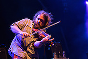 Ryan Young, the fiddler for Trampled by Turtles, on stage at Celebrate Brooklyn. Young plays an athletic fiddle, often bending himself at the waist.