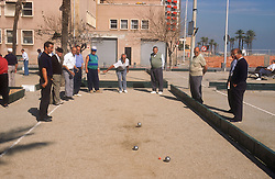 Group of men playing game of boules in street,