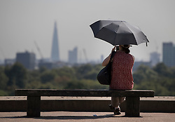 © Licensed to London News Pictures. 24/08/2016. London, UK. A woman takes shelter from the heat under an umbrella on Primrose Hill. London is experiencing a second day of high temperatures with a peak of 30 degrees expected. Photo credit: Peter Macdiarmid/LNP