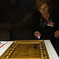 PADOVA, ITALY - APRIL 13:  One of the curator of the museum carefully inspects one of the paintings by Guariento which will be on display on April 13, 2011 in Padova, Italy. The Guariento exhibition will be open from April 16th until July 31st in the renovated Foundation Cariparo in Piazza del Duomo.