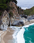 McWay Falls pours into the Pacific Ocean at Julia Pfeiffer Burns State Park in Big Sur, California as the Pacific Ocean laps at the shore.