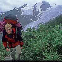 13-year old Ben Wiltsie slogs a huge pack of mountaineering equipment up the long, steep trail to the Conrad Cain hut, a haven for climbers. Behind him is the Bugaboo Glacier.