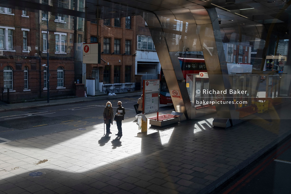 Two passengers wait for their next bus at Vauxhall Bus Station in south London, on 5th October 2020, in London, England.