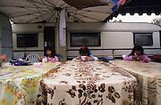 Three Gitan girls have breakfast outside their family's caravan. St Jean du Gard, France summer 1995