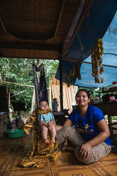 Loklahung, Indonesia - February 28, 2017: Daowi sits next to her five-month-old child Regina in a swing chair in a village in Loklahung, South Kalimantan, located on the island of Borneo