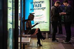 © Licensed to London News Pictures . 28/10/2018. Manchester, UK. A woman wearing a halo sits at a bus stop amongst revellers on a night out in the Northern Quarter of Manchester City Centre , on the weekend before Halloween . Photo credit: Joel Goodman/LNP