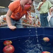 "October 6, 2007 -- BATH, Maine. Violet Fraser, 5, of Bath tries apple bobbing for the first time at Gediman's in Bath on Saturday afternoon during Autumnfest. ""You just have to go underwater,""  she said of her technique. ""And,  pushing the apple against the side helps too.""  Patty Bellavance, manager at Gediman's hosted the event, and said, ""I was afraid it was too old fashioned."" But by the end of the afternoon, more than 14 children (at heart) had successfully bobbed for apples. Photo by Roger S. Duncan."