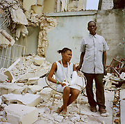 "Claudette, thirty-three has five kids. She is  photographed with her father, Crispin, sixty-six in their neighbourhood as it is now. She feels lucky to have escaped. ""I was buying some drinking water with my son, Gito and was on the way back  when the ground started rumbling. I cried out, `wow an earthquake!` At that point I looked up to see a two- storey building falling down on me. Large blocks of masonry trapped my arm and fell on my son . My son got free and  went for help. Five men returned and tried to lift the masonry with a large stick but they couldn't do it, they left me. I was petrified, the house next door caught alight and I knew for sure I was going to die"" Then I felt someone pulling my arm although no one was there. From that moment I struggled to free myself, I pulled so fiercely that I left my finger behind  It wasn't until two hours later that I realized."""