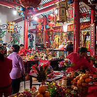 """Village ladies, dressed in lucky red clothing, put last minute touches on the elaborate food offerings placed before the altar of the Mazu, where the temple's icon is placed.  Food offerings are given in thanks for the goddess's protection.<br /> <br /> Mazu was once a living woman, a local shamaness who, through her exceptional deeds, was able to ascend to the pantheon of gods. Over the past millennia veneration of Mazu evolved from this one small island to now having an estimated 4000 temples in China alone and thousands more worldwide. Far from being described as a shamaness her title is Tianhou, or """"Heavenly Empress"""" conferred to her in 1683."""