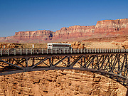 Our Arizona Raft Adventures bus crosses the new 1995 Navajo Bridge in Grand Canyon National Park, near Fredonia, Arizona, USA. The new bridge was completed in 1995. I captured this image while standing on the original Navajo Bridge which was built in 1929. Highway 89A crosses the Colorado River here at River Mile 4.5 (measured downstream of Lees Ferry where we would launch rafts just 2 hours later).