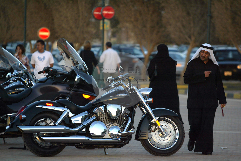 Kuwaities in traditional attire walk past Harley Davidson motorcycles at a shopping mall in Kuwait City.
