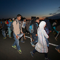 Illegal migrants walk with police escort on highway M5 after they broke out and run away from custody through a line of police officers near Roszke (about 174 km South of capital city Budapest), Hungary on September 07, 2015. ATTILA VOLGYI
