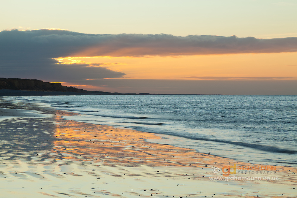 Colourful evening skies reflect in a sandy section of Sheringham beach. North Norfolk, East Anglia.