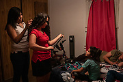 Rachel, daughter of Orfa, an asylum seeker from Honduras, looks up at older sister Carolina as her hair is curled in anticipation of Christmas Eve festivities in the family's trailer in Texico, New Mexico, U.S., December 24, 2018.