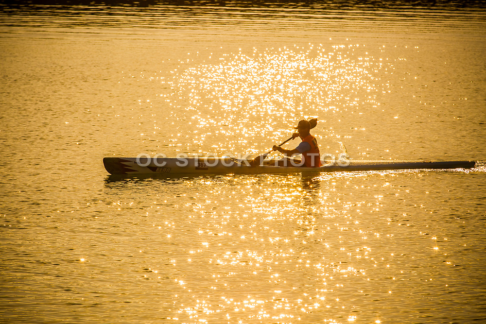 Man Paddling a Kayak in the Ocean at Sunset