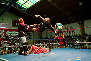 Male wrestler doing a flying kick move to opponent with female wrestler on the floor. Lucha Libre wrestling origniated in Mexico, but is popular in other latin Amercian countries, including in La Paz / El Alto, Bolivia. Male and female fighters participate in the theatrical staged fights to an adoring crowd of locals and foreigners alike.
