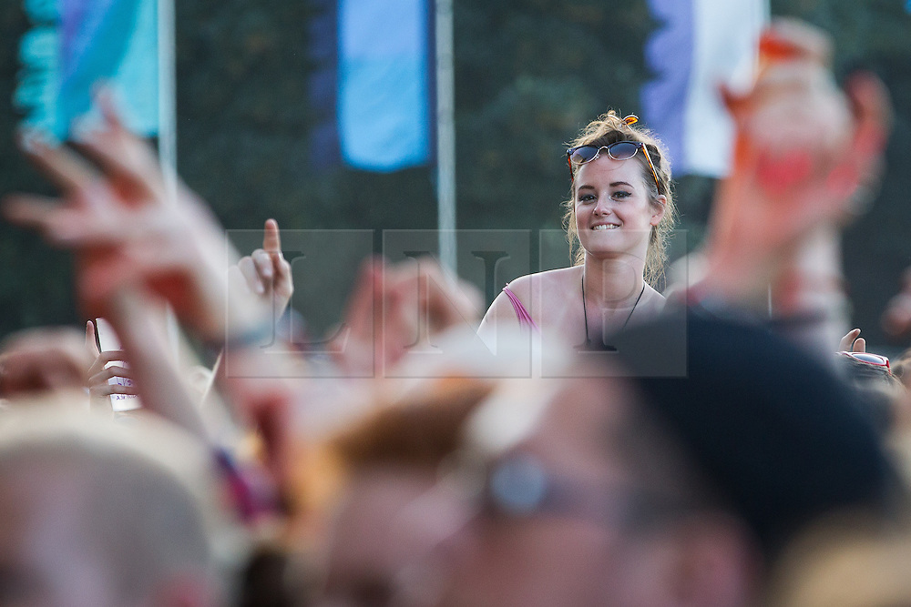 © Licensed to London News Pictures . 19/07/2013 . Suffolk , UK . A woman watches The Maccabees perform on the Obelisk Stage . The Latitude music and culture festival in Henham Park , Southwold . Photo credit : Joel Goodman/LNP