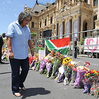 CAPE TOWN, SOUTH AFRICA - Saturday 7 December 2013, Executive Mayor of Cape Town, Mrs Patricia De Lille, reads some of the condolence messages on some of the numerous bunches of flowers during a time of national mourning the death of the first democratically elected president, Nelson Mandela, in front of the Cape Town City Hall.<br /> Photo by Roger Sedres/ImageSA