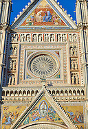 Close up of a gable with mosaics depicting the the Virgin Mary created between 1350 and 1390 after designs by artist Cesare Nebbia and the rose window built by the sculptor and architect Orcagna between 1354 and 1380 on the14th century Tuscan Gothic style facade of the Cathedral of Orvieto, designed by Maitani, Umbria, Italy .<br /> <br /> Visit our ITALY HISTORIC PLACES PHOTO COLLECTION for more   photos of Italy to download or buy as prints https://funkystock.photoshelter.com/gallery-collection/2b-Pictures-Images-of-Italy-Photos-of-Italian-Historic-Landmark-Sites/C0000qxA2zGFjd_k<br /> .<br /> <br /> Visit our MEDIEVAL PHOTO COLLECTIONS for more   photos  to download or buy as prints https://funkystock.photoshelter.com/gallery-collection/Medieval-Middle-Ages-Historic-Places-Arcaeological-Sites-Pictures-Images-of/C0000B5ZA54_WD0s