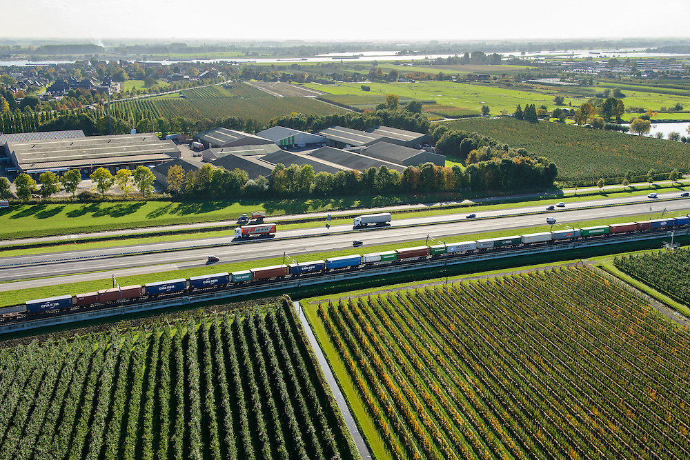 Nederland, Gelderland, Betuwe, 24-10-2013; Betuweroute, ter hoogte van Echteld. De goederenspoorlijn loopt parallel aan autosnelweg A15. De goederentrein is onderweg naar de haven van Rotterdam. De weg en het spoor lopen tussen de boomkwekerijen.<br /> Betuweroute, railway from Rotterdam to Germany, near Echteld. The freight railway runs parallel to highway A15. The freight is on its way to the port of Rotterdam.<br /> luchtfoto (toeslag op standaard tarieven);<br /> aerial photo (additional fee required);<br /> copyright foto/photo Siebe Swart.