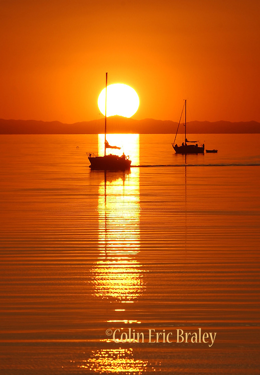 Sailboats are silhouetted as the sun sets on a warm summer day on the Great Salt Lake in Utah.